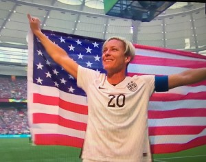 Abby Wambach holding the US flag after winning the World Cup